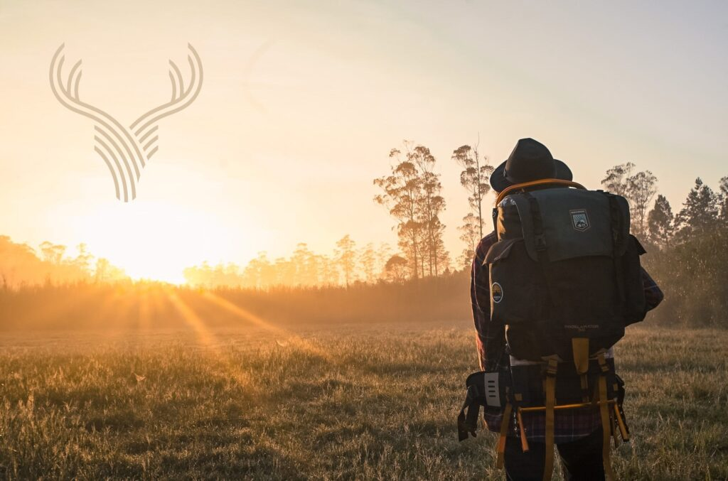 Image of hiker walking into sunrise